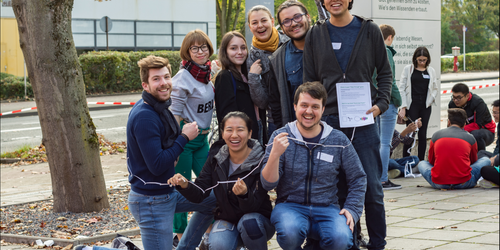 a group of international students in front of the International Meeting Center of the TU Dortmund University playing a game; in the background another group
