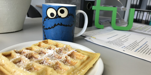 in the foreground a waffle and a cup with an imprint of the Cookie Monster of Sesame Street, in the background a file folder