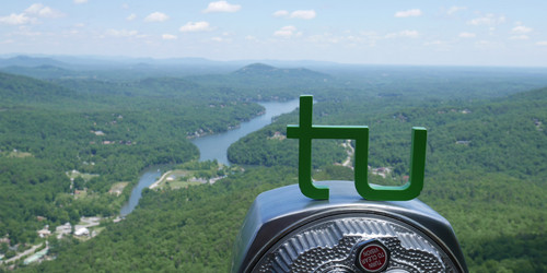 TU Logo on binoculars with a view on a river landscape
