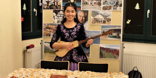an Asian woman playing the guitar at the International CultureCafé (IKC)