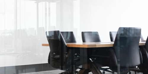 Black office chairs next to a brown table in a conference room