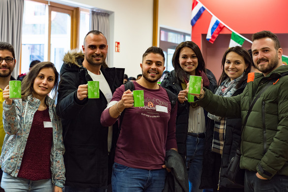 a group of international students with TU Dortmund University cups in their hands, smiling into the camera